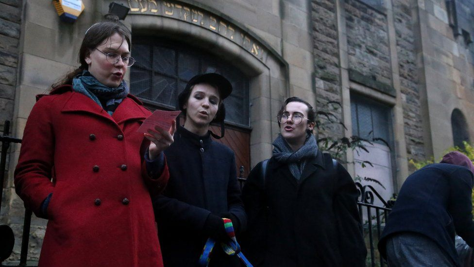 Jewish people singing outside the synagogue in the rain