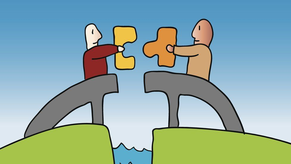 Two men holding separate pieces of a puzzle over a rift