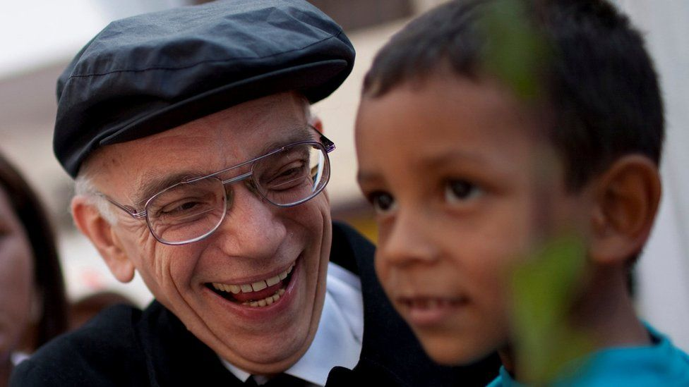 José Abreu meets a child as he arrives at a free concert at La Vega in Caracas August 2, 2009