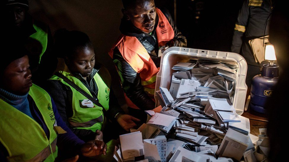 """An election official opens a ballot box during the tally of the votes at a polling station for the general election in the suburb of Mbare of Zimbabwe""""s capital Harare on July 30, 2018"""