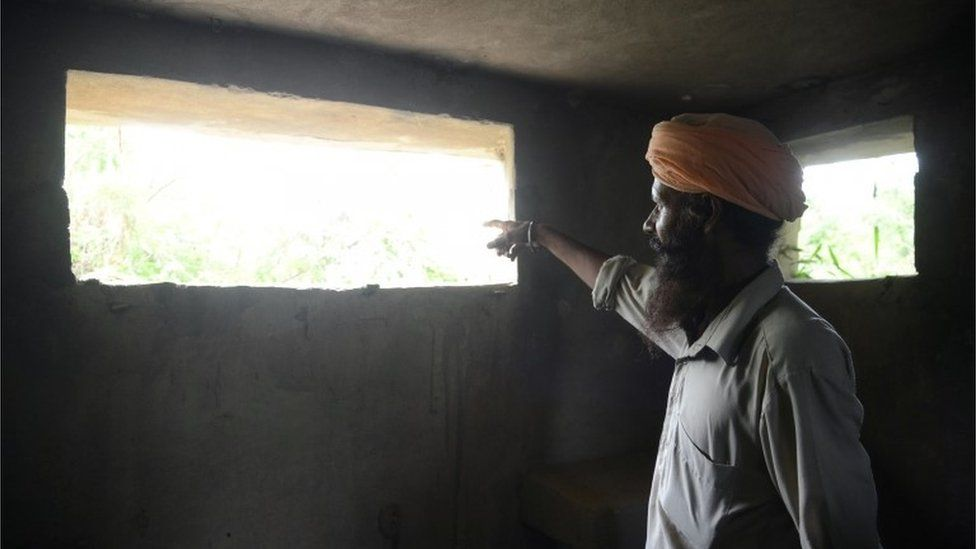 An Indian border area villager looks out of a military bunker at the Indian/Pakistan border village Chak Allah Bakash, about 45km from Amritsar on September 30, 2016,
