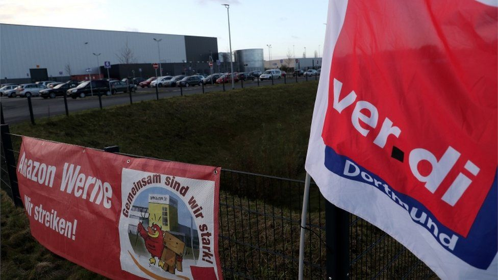 """A trade union protest banner reads, """"Together we are strong! We are on strike"""", on a fence of the Amazon logistic centre in Werne, Germany, 29 November 2019"""