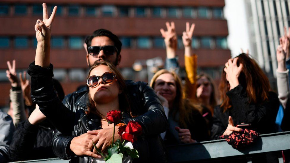 People flash the victory sign as they attend a memorial ceremony at Sergels Torg plaza in Stockholm, Sweden on April 9, 2017