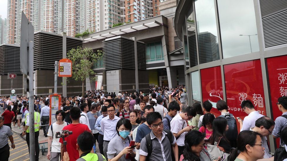 Stranded train passengers queue for a shuttle bus after Anti-extradition bill protesters disrupted train services