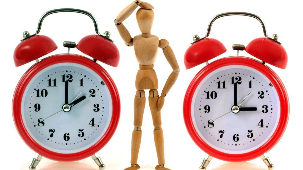 A mannequin looks puzzled beside two clocks