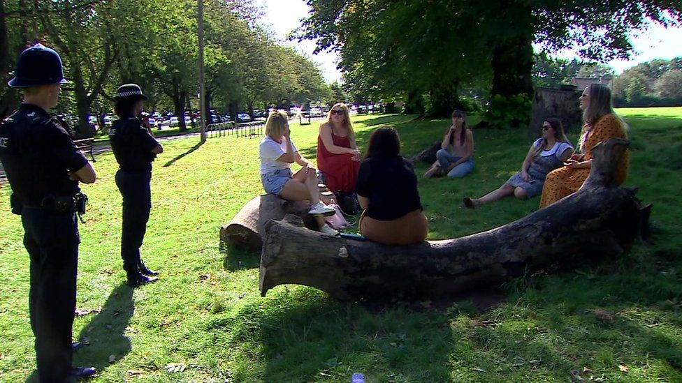 A group of students in a Bristol park with police enforcing coronavirus restrictions
