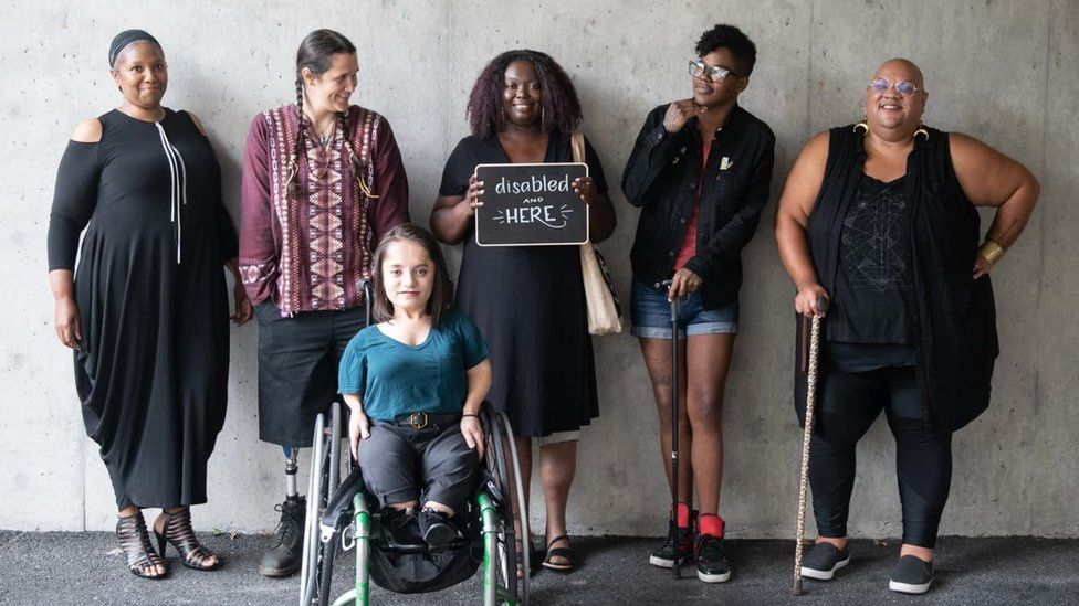 Collection of women holding a 'Disabled and here' sign