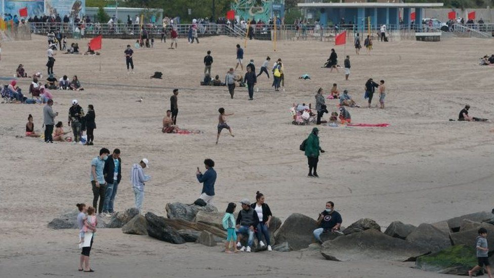 People enjoy staying on the beach as swimming is not allowed at Coney Island, New York. Photo: 24 May 2020