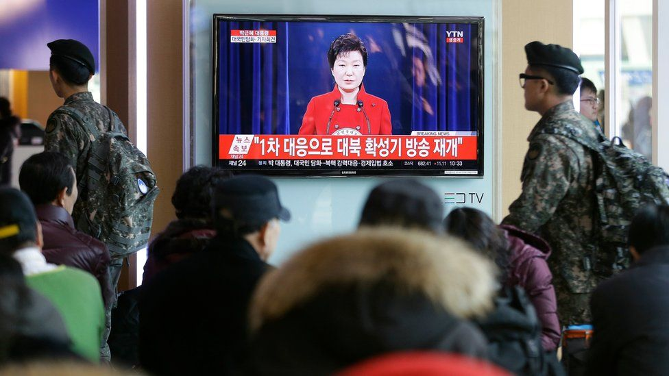 People watch a TV screen showing the live broadcast of South Korean President Park Geun-hye's press conference