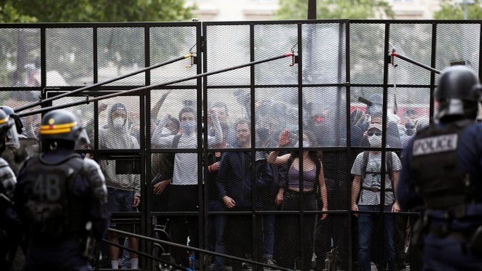 Demonstrators are seen behind a fence as they protest against police brutality and the death in Minneapolis police custody of George Floyd, at the Place de la Republique square in Paris 13 June