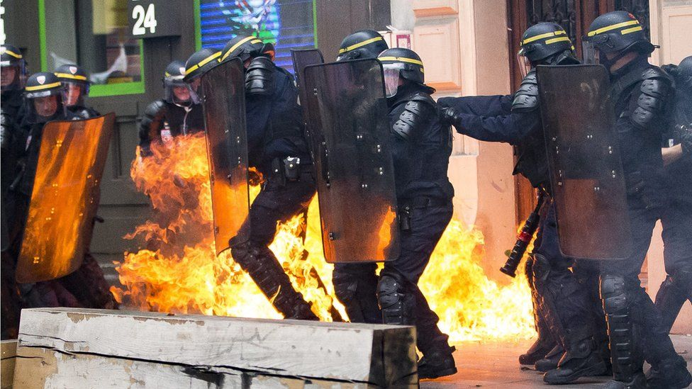 A molotov cocktail explodes next to French riot police