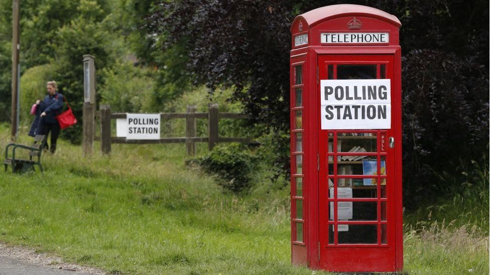 A telephone booth with a polling station sign