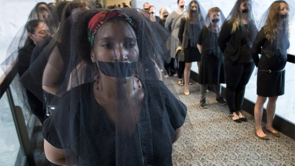 Women with black veils and black tape over their mouths in protest of Kavanaugh line up outside the hearing room
