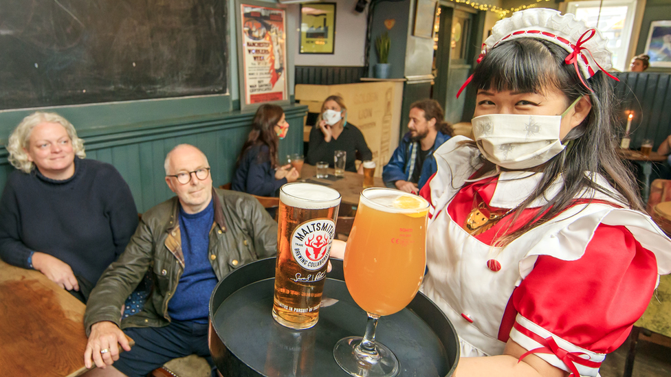 Woman in mask serves drinks to pub customers