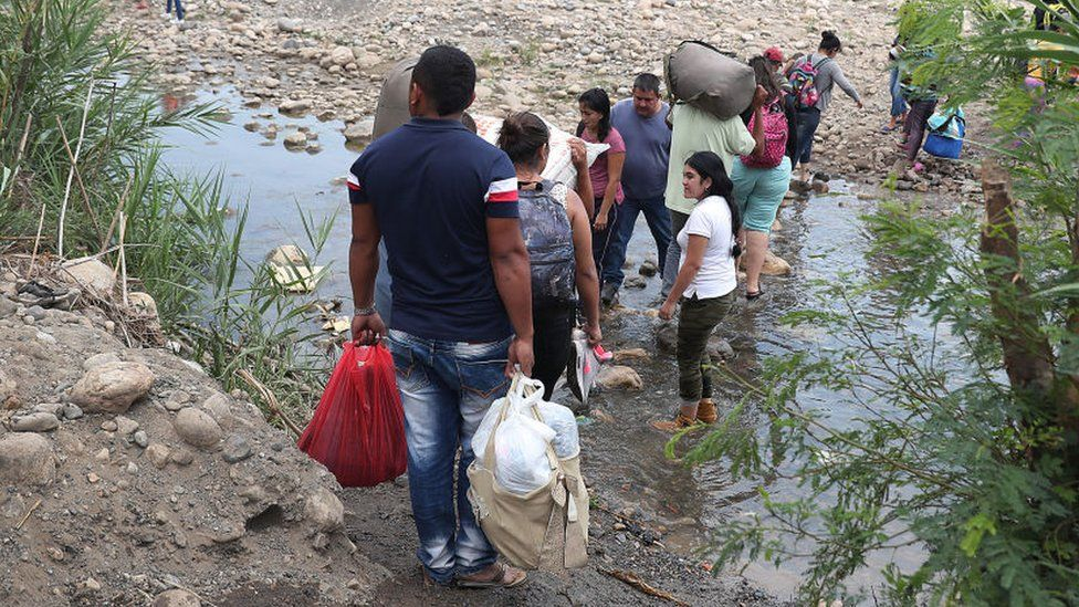 People cross through the low waters of the Táchira River near the Simón Bolívar international bridge, which connects Cúcuta with the Venezuelan town of San Antonio del Táchira, after the closure of the border bridge on February 27, 2019 in Cucuta, Colombia.