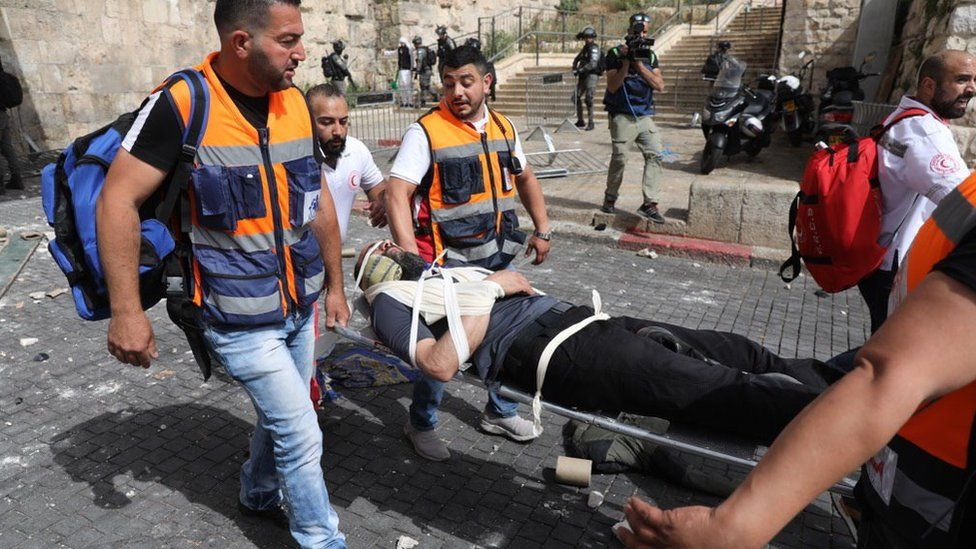 Palestinian medics carry a wounded man on a stretcher at the Lions' Gate of Jerusalem's Old City