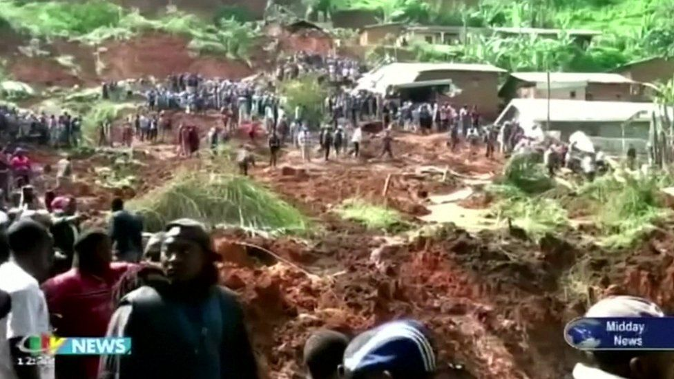People looking on as the area of the mudslide is searched
