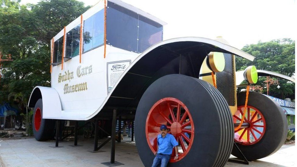 Indian car designer Sudhakar Yadav poses next to a large stationary car - modelled on the 1922 Ford Tourer - at the Sudha Cars Museum in Hyderabad