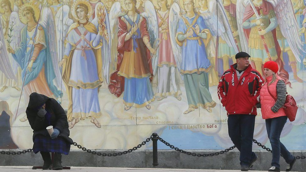 An old Ukrainian woman begs for money in front of Mikhailovskiy Cathedral frescos in downtown Kiev