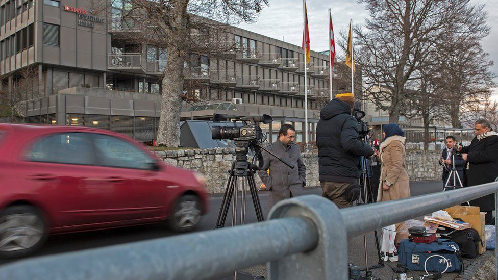 Journalists stand outside Swiss Olympic House in the Swiss village of Macolin, near the town of Biel (15 December 2015)