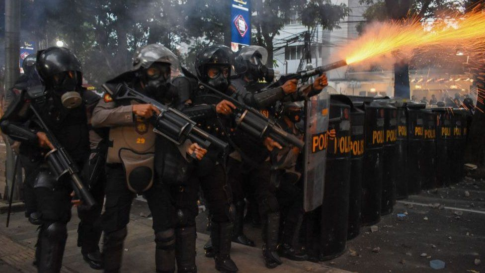 Indonesian riot police disperse protestors with tear gas in Bandung on Wednesday.