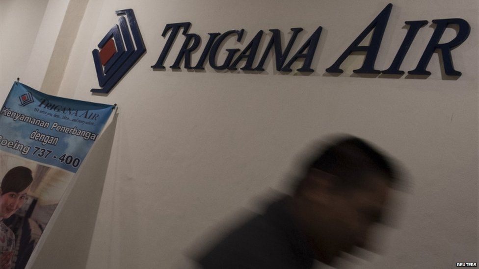 A man walks past the Trigana Air Services logo at the airlines office in Jakarta 16 August 2015 in this photo taken by Antara Foto.