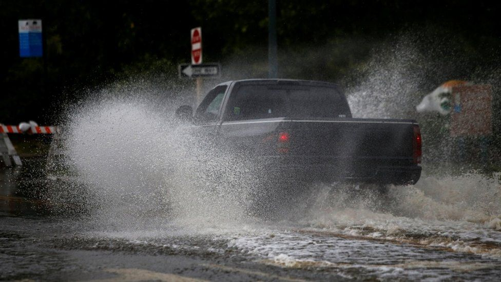 A man drives his vehicle around the Union Point Park Complex through floodwaters as the Hurricane Florence comes ashore in New Bern