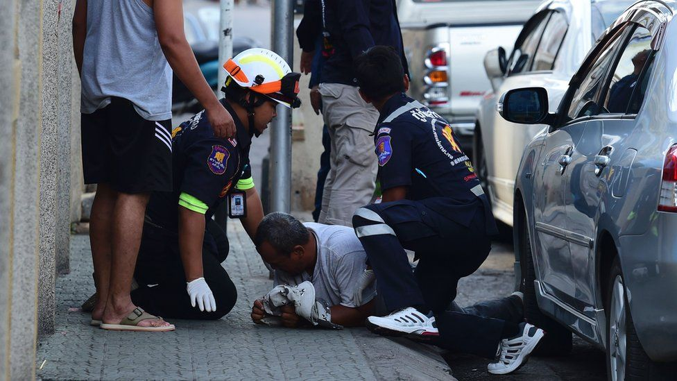 Emergency services personnel attend to a man injured in one of the blasts in Hua Hin, 12 August 2016.
