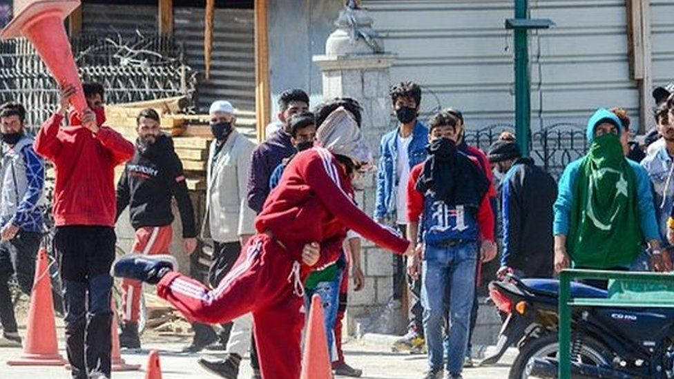 A Kashmiri protester throws a stone at government forces during the demonstration against the revocation of Article 370.