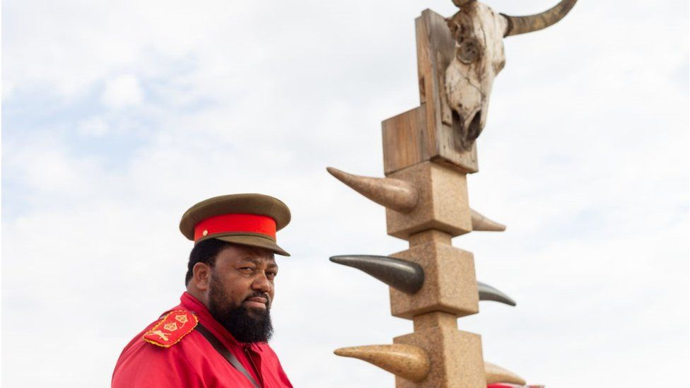 A high-ranking chief in traditional Herero clothes stands next to a monument in honour of the OvaHerero/OvaMbanderu and Nama people that were victims of the genocide by German colonial forces at the beginning of the 20th century stands at the Swakopmund Concentration Camp Memorial, in Swakopmund, Namibia, on March 27, 2019