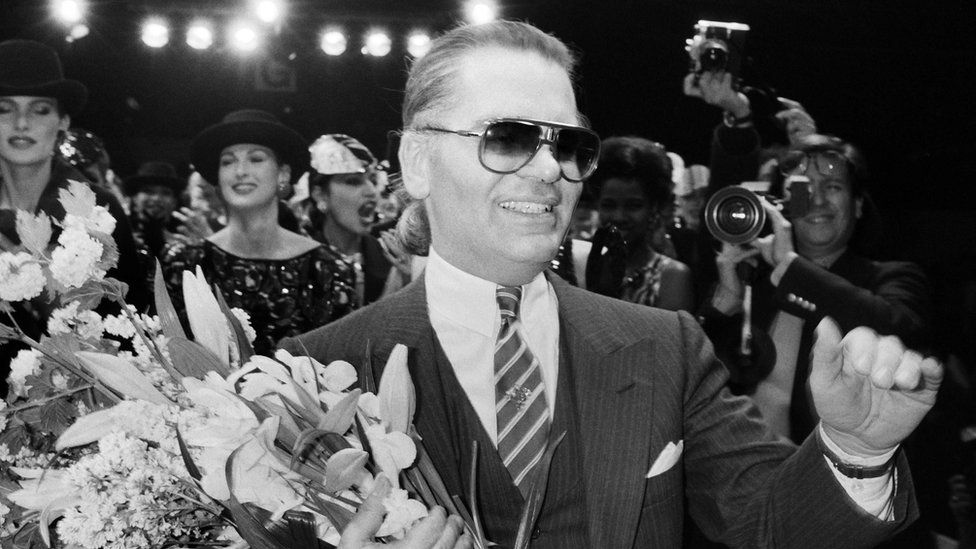 March 27, 1984 German fashion designer Karl Lagerfeld, flanked with models, acknowledges the public after the Chanel autumn-winter 1984/1985 ready-to-wear collection show in Paris