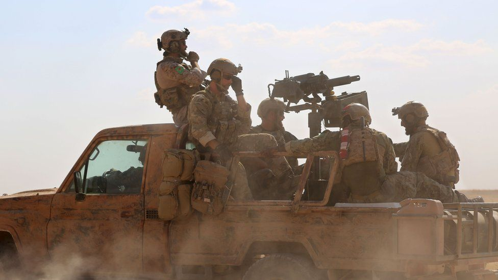 Armed men in uniform identified by Syrian Democratic forces as US special operations ride in the back of a pickup truck in the northern Syrian province of Raqqa on May 25, 2016.
