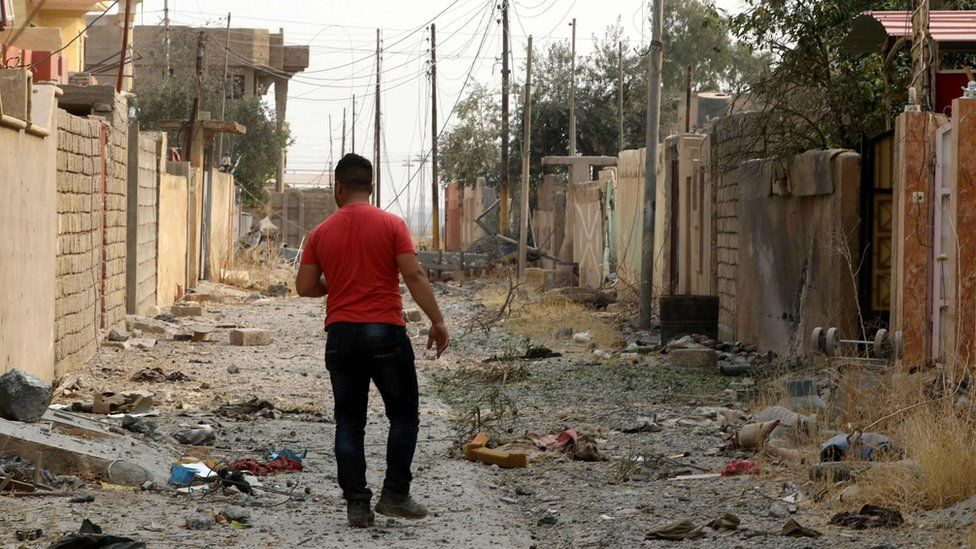 A man inspects damage in the Christian Iraqi town of Bartella, east of Mosul, after its recapture by government forces (24 October 2016)