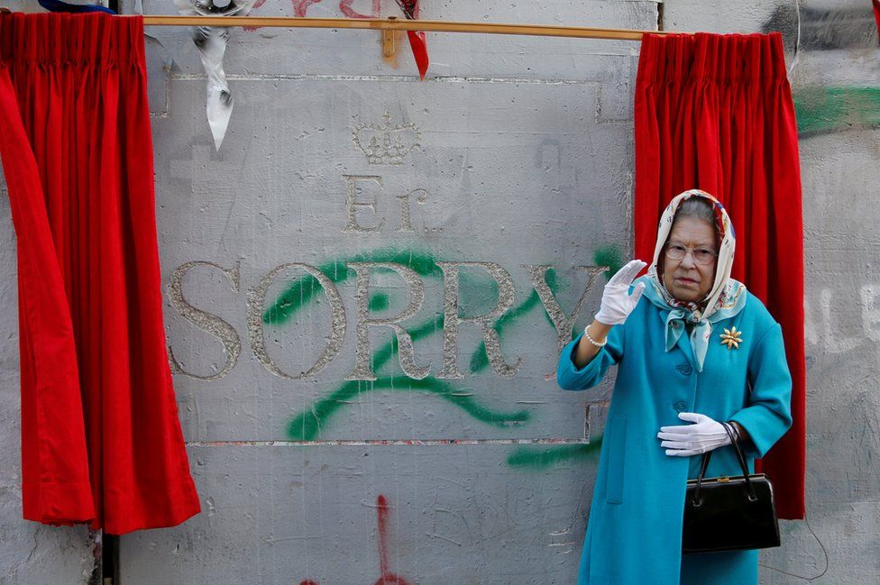 An actor dressed as Britain's Queen Elizabeth II, gestures during an event ahead of the anniversary of the Balfour Declaration, outside Banksy's Walled Off Hotel in the West Bank city of Bethlehem, 1 November 2017.