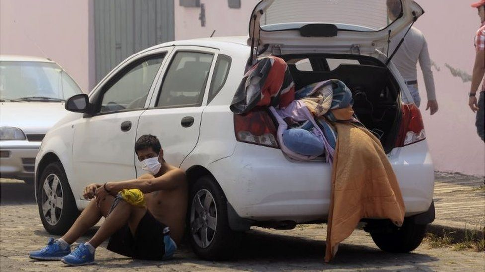 A man rests next to his car as he prepares to leave his house during a forest fire in the hillsides around Quito, on 15 September, 2015.