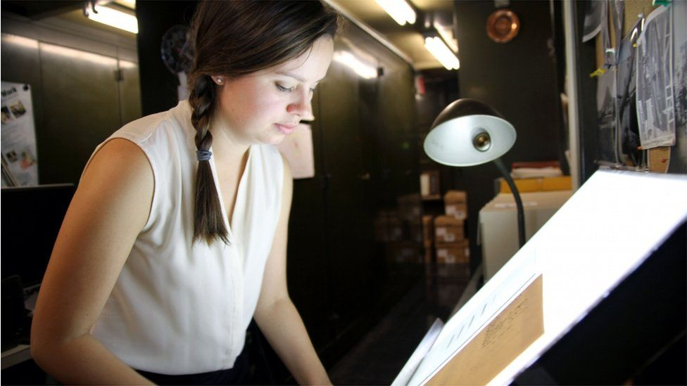 Curator Lindsay Smith Zrull places a glass plate photograph of a section of the sky onto a lightbox