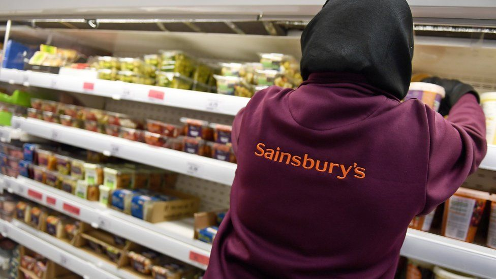 A Sainsbury's worker places products on a shelf