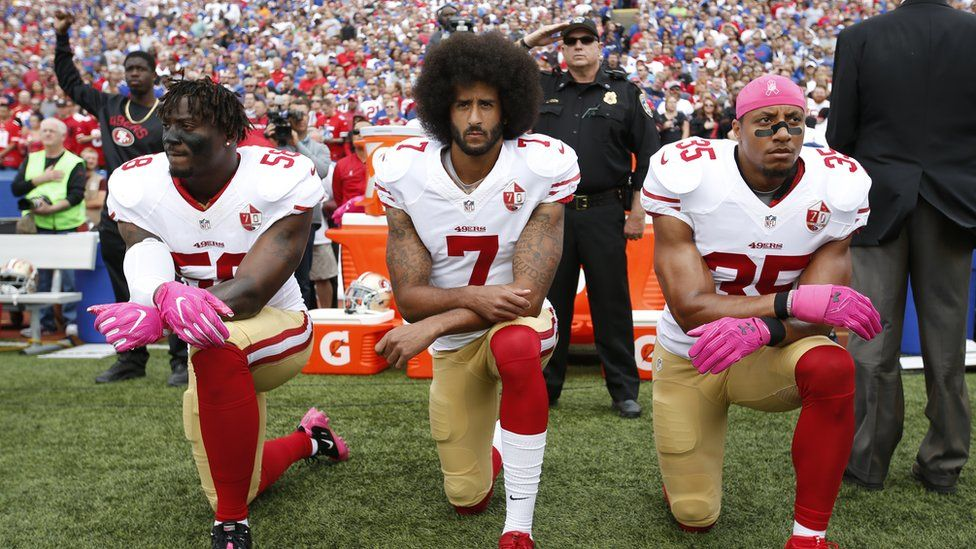 Eli Harold, Colin Kaepernick and Eric Reid kneel in protest on October 16, 2016