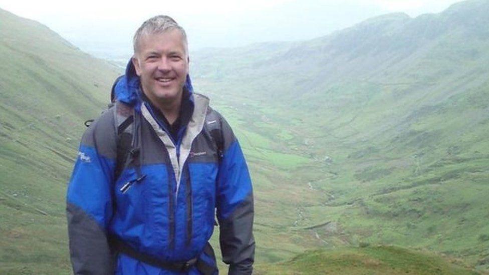 Derek Brockway yn y glaw wrth ffilmio 'Weatherman Walking' i'r BBC