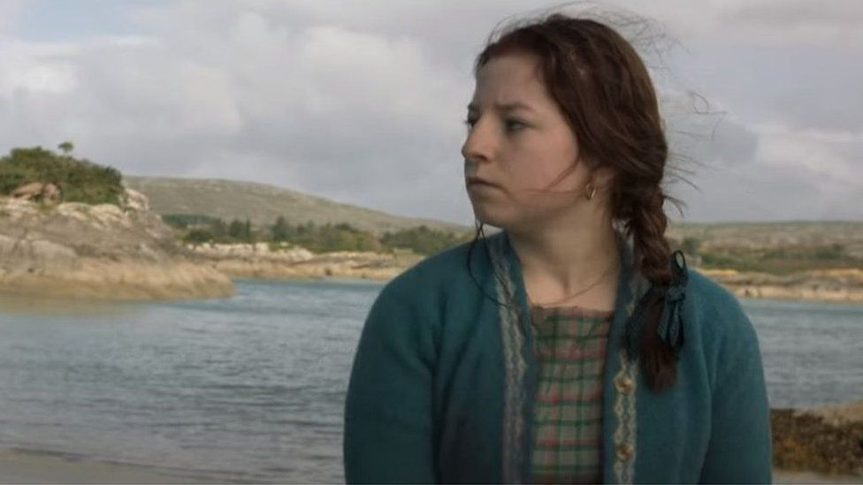 A still from the film Float Like a Butterfly, showing lead actor Hazel Doupe against an outdoor backdrop next to water