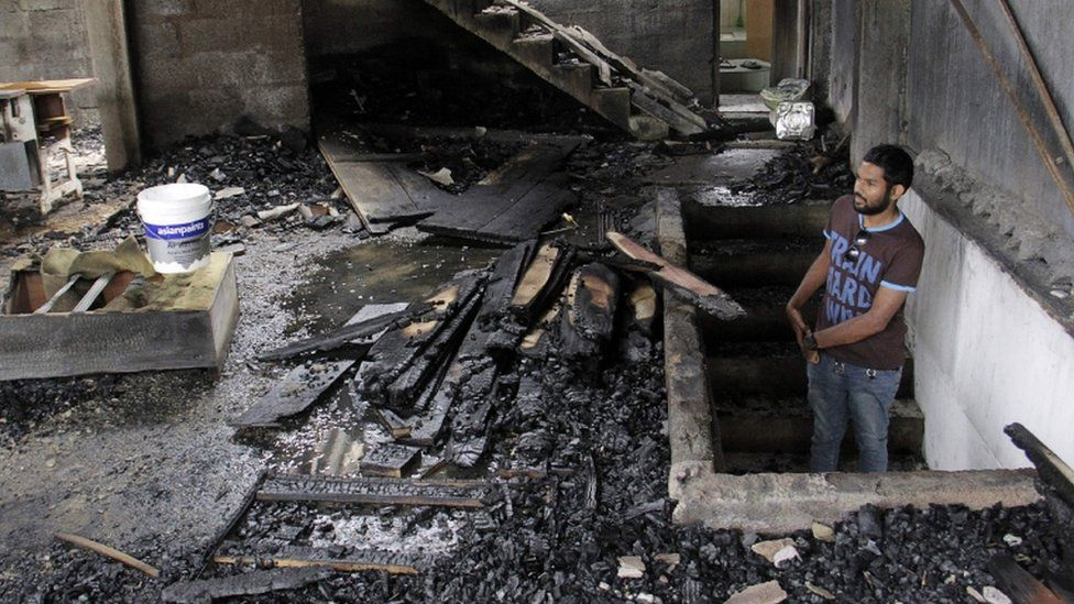 A man assesses damage to burned home in Digana, in Kandy on March 7