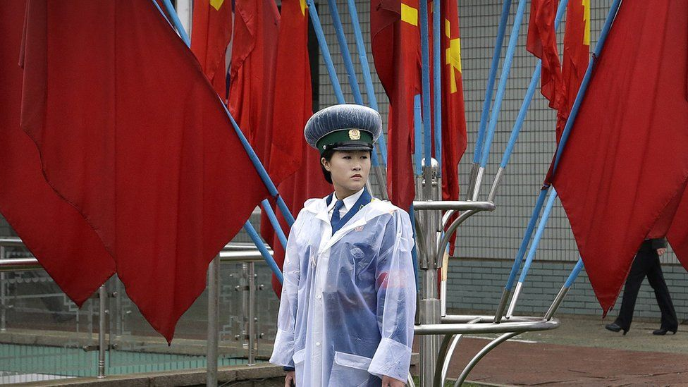 A North Korean traffic woman stand in front of flags