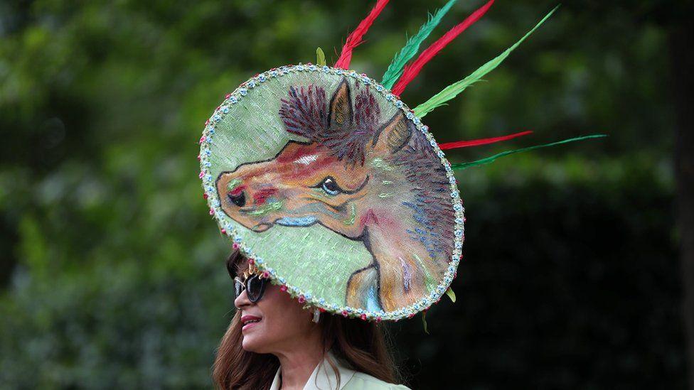 женщина в шляпе, где изображена голова лошади