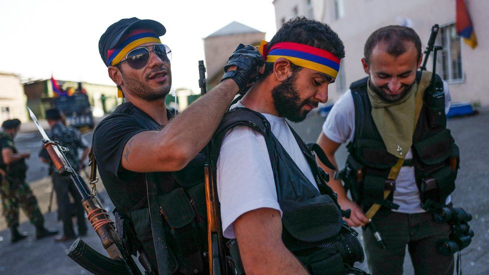 Gunmen wear Armenian national colours as they guard a seized police station in Yerevan, 23 July 2016