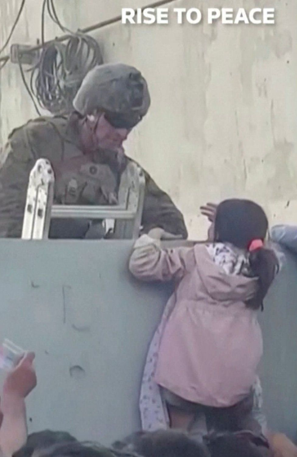A girl is helped over a wall at Kabul airport