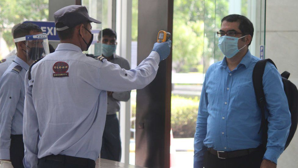 A security guard thermal screens people as they enter an office building at Park Centra in Sector 30, on June 8, 2020 in Gurugram, India.