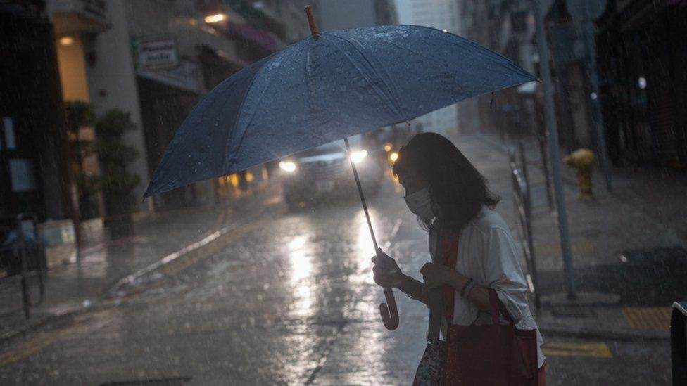 A woman carries an umbrella as she crosses a street during a rain storm in Hong Kong.