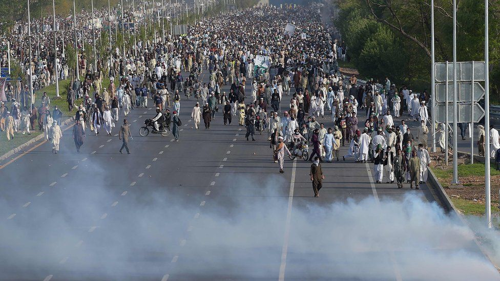 Supporters of executed Islamist Mumtaz Qadri walk through tear gas fired by police officers