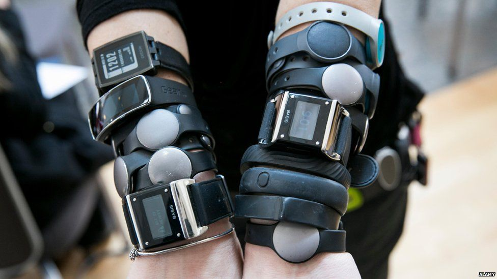 Arms covered in fitness devices.