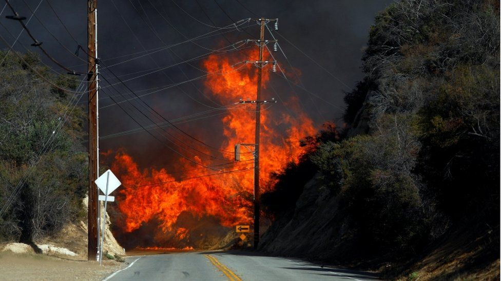 Flames from a wildfire are seen on a road in California